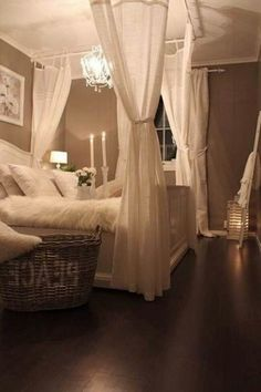 The warm lighting and the white canopy bed gives the bedroom a cozy and romantic atmosphere.