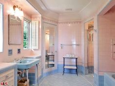 This Art Deco bathroom looks original with the pink and blue tile.