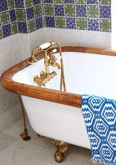 A wooden and porcelain clawfoot tub with gold fixtures