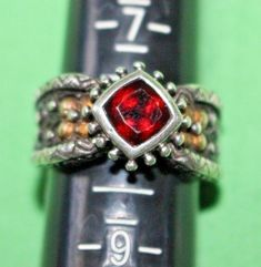 Beautiful ornate ring designed by Barbara Bixby. Sterling Silver with solid Gold flowers on each side of the carat garnet, and a Sterling Silver flower on the bottom of band. Garnet Rings, Sterling Silver Flowers, Gold Flowers, Ring Designs, 18k Gold, Diamond Earrings, Jewelry Watches, Fine Jewelry, Etsy Shop