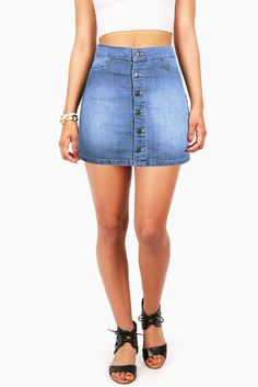 """Adorable denim mini skit with an A-line construction. Button up closure down the front with pockets at sides. Stretchy denim skirt fit can be worn mid or high waist. Pair it with a tucked in graphic tee for a casual look. *Machine Wash Cold*79% Cotton 19% Polyester 2% Spandex*15""""/38 cm Top to Bottom- Measured on a Size M (Model is 5'5/wearing size S) *Refer to Bottoms Size chart #2*Imported"""