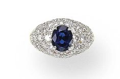 A SAPPHIRE AND DIAMOND RING, BY CARTIER   Set with an oval-cut sapphire within a bombé pavé-set diamond mount, mounted in 18K gold and platinum  Signed Cartier