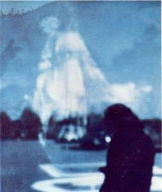 A photo taken of John M. (foreground), approximately 70 yards from the site of the Vatican Pavilion in Flushing Meadows Park Queens NY (situated at the bottom of Our Lady's Mantle). Miraculously, the Blessed Virgin Mary, the Mother of God appears on the photo dominating the sky above Her chosen Sacred Grounds. The fingers of Our Lord (top left) are pointing toward Our Lady, as if to say, 'behold your Mother!' This incredible photo clearly shows Our Lady's true presence on Her Shrine Grounds.