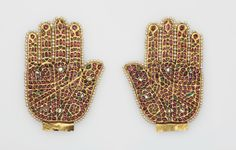 Finial in the Shape of the 'Hand of Fatima'. Possibly Hyderabad (India), late 18th-early 19th century. Gold on a lac core, rubies, emeralds, diamonds, and pearls, 11.8 cm. Nasser D. Khalili Collection, London (JLY1923) © Nour Foundation. Courtesy of the Khalili Family Trust