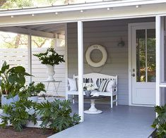 This cottage home's crisp white and nautically inspired decor starts at the front door. White structural elements, such as the beams and pillars, delineates a palette of grays. A hand-painted life raft boasts the home's address. White Cottage, Cozy Cottage, Cottage Homes, Cottage Ideas, Exterior Colors, Exterior Paint, Cottage Style Front Doors, Lakeside Cabin, Cottage Exterior