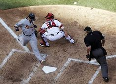St. Louis Cardinals' Yadier Molina, left, scores a run in front of Washington Nationals catcher Kurt Suzuki on a sacrifice fly by Daniel Descalso in the sixth inning of Game 3 of the National League division baseball series against the Washington Nationals on Wednesday, Oct. 10, 2012, in Washington. Home plate umpire Joe West, right, watches the play.