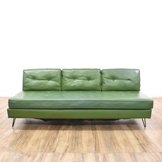 This mid century modern sofa is upholstered in a durable vinyl with a shiny dark green finish. This retro couch has tufted cushions, a low back and black metal hairpin legs. Stylish and sleek daybed great for lounging! #midcenturymodern #sofas #sofaorcouch #sandiegovintage #vintagefurniture