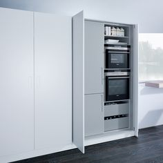 Witte keukenkasten waar de apparatuur is weggewerkt achter inschuifbare kastfronten - next125