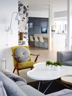 GODT MED LUFT: Takhøyden i stuen er på 3,4 meter.Kjøkkenet er fra Kvik, med benkeplate i Corian bestiltpå mål fra Tyskland. Lenestolen er et bruktfunn.Gulvteppet er fra Hay. For å skape dynamikk i detåpne rommet, valgte beboer å tapetsere en vegg medmønstret tapet fra Scandinavian Surface.