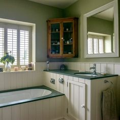 Green country bathroom with white shutters