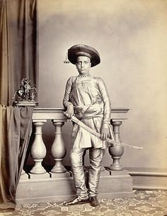 The son of H.H. Chunnasee Rajoonath Pant by Bourne and Shepherd in the late 1860s, from the Archaeological Survey of India Collections. The youth in this photograph is holding a sword, leaning a against a banister rail beside a sculptural ornament of a horse and archer. .