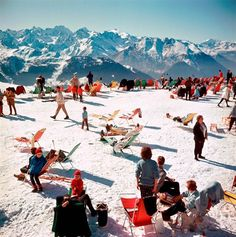 Skiers relax in deckchairs on the slopes at Verbier in Switzerland, Slim Aarons, 1964.