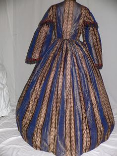 1860s silk striped dress, blue horizontal stripes alternating with brown and beige double patterned stripe. Sleeve cap w navy and rust fringe. Bodice lined with cotton; 5 stays in the front .Closure is inner cotton tab with hooks and regular eye hooks down the front. Pagoda sleeves lined in tan cotton w last 5 inches lined in blue silk. Bodice joined to skirt with cartridge pleating. 12 inch tan cotton lining at hemline, pocket in one side seam. Skirt approx 130 inches.