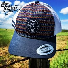 """A fun """"go-to"""" hat! This HOOey hat features a multi colored zig zag Aztec print with a navy blue background. A navy and white patch on the front with the HOOey hands up logo in white. The back mesh is white with a navy snapback closure. One size fits all. Carhartt Overalls Women, Baseball Cap Hairstyles, Hooey Hats, Hat Stores, Cheap Sandals, Country Girls Outfits, Cowgirl Hats, Navy Blue Background, Dress Hats"""