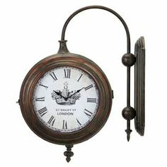 "Wall-mounted train station-style clock with an antiqued brass finish.     Product: Wall clock    Construction Material: Iron metal    Color: Antique brass    Features:Two-sided design Roman numerals on crown dial   Accommodates: (2) AA batteries - not included   Dimensions: 21.9"" H x 17.3"" W x 4"" D      Cleaning and Care: Wipe with soft dust cloth"
