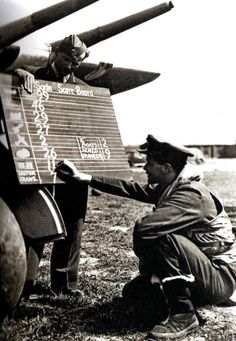 A RAF pilot chalks up the score of his Hawker Typhoon Mk 1B aircraft on the Squadron board UK - 6 June - 1944