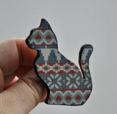 Kočka v norském svetru Kočička na klopu ze dřeva a kvalitního scrapbookového papíru, patinováno, přelakováno. Zapínání na brožový můstek. Brož je lehounká, může proto být i na tričku, samozřejmě také na svetru či klopě kabátu.