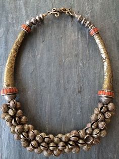 Djore Designs - small antique brass pendants from the Republic of Cameroon, made using the lost wax method. The two antique repousee cones are from Tibet, and they have natural inlaid coral. With silver biconebeads from Ethiopia