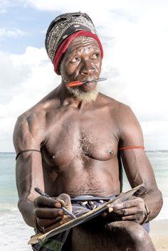Portret van de Strandman op Coco Beach, Dar es Salaam, Tanzania. Deze strandjutter verdient wat geld bij door portretten van 'rijke' touristen te tekenen