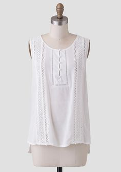 Stylish and cute, this white blouse features a variety of sheer lace trim at the front with covered buttons at the bust.