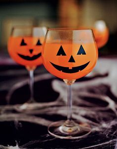 Haloween! Olhos, nariz e boquinha feitos de cartolina preta e colados na taça contrastam com o refrigerante laranja