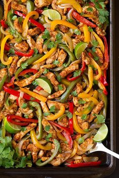 Chicken Fajitas on baking sheet with cilantro and limes