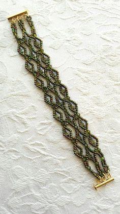 Olive Green diamond beaded lattice crystal lacy cuff bracelet using Swarovski crystal elements. Genuine Swarovski Olivine colour crystals surrounded by a handsewn net of metallic green iris seed beads and lustred olive green glass diamond shape (DiamonDuo) beads, showing beautiful