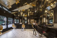 the barber shop features a golden reflective ceiling that mirrors the interior of the space.