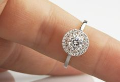 One of the most beautiful modern, yet vintage styled diamond halo rings with an exquisite balance of diamonds in a wedding ring friendly setting and plain band.
