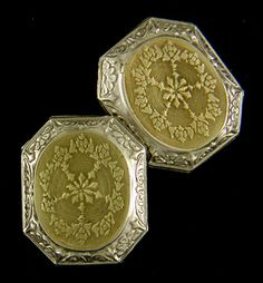 Elegant two-tone cufflinks with intricately engraved yellow gold centers surrounded by dramatic white gold borders of alternating scrolls and stylized flower or sunrise motifs.  Crafted in 14kt gold,  circa 1920.