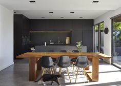 """M House is a minimalist house located in Melbourne, Australia, designed by DKO. The kitchen space features porcelain 'Maximum Moon' throughtout, blacked out custom cabinetry with a black kitchen island that achieves a strong """"masculine"""" look. In..."""