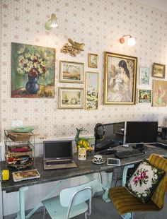 A collection of pictures and vintage lamps that were found and bought in various flea markets around the world and hung on vintage wallpaper  found on eBay serve as a working inspiration board in this home in Israel.