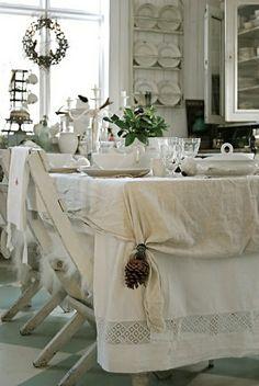 une table avec nappe blanche en lin, set de table élégant, plantes vertes sur la table