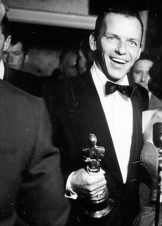 Frank Sinatra beams while speaking to reporters backstage after his Oscar win, 1954.
