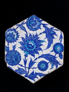 Tile | Made in Iznik, Turkey, ca. 1525-1550 | Materials: fritware, underglaze painted in cobalt blue and turquoise, glazed | Tile of buff-coloured fritware, painted in dark blue and turquoise-blue on a white slip and covered with a clear glaze. Hexagonal in shape and the design consists of palmettes, flowers and serrated leaves on curved interlacing stems | VA Museum, London