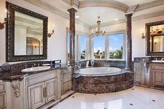Classical corner bathtub with dark brown stone exterior, rustic vanity cabinetry.