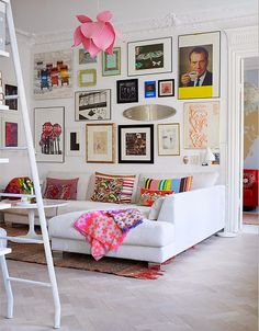 Floor to ceiling gallery wall, large crown molding, white sectional, bright and funky living room