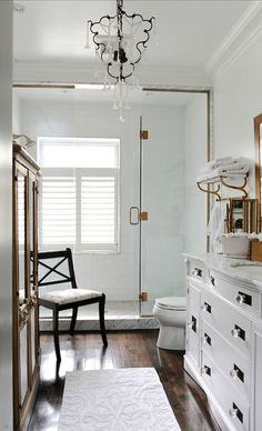 Stunning bathroom features walls painted Benjamin Moore White Cloud highlighting a glass shower tiled in subway tile which frames a plantation shuttered window over mini mosaic tiled shower floors.