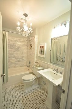 White subway tile, half tiled wall with chair rail, traditional bathroom, basketweave marble tile floor, pedestal sink, chandelier.