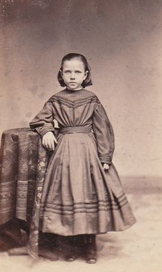 1860s girls dress from st. louis, mo. interesting that she does not have a center part.