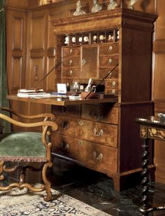 A WILLIAM III BURR AND FIGURED WALNUT FALL-FRONT SECRETAIRE CABINET the fall front opening to a central prospect door opening to a bank of three drawers, the prospect surmounted by two banks of three pigeon holes which slide forward to reveal secret drawers, and flanked by a bank of three drawers above a long drawer and niche, the bottom of the niche fitted with a sliding panel sliding forward to reveal a secret well and two and two secret drawers  LATE 17TH CENTURY