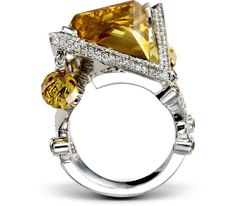 This orange sapphire and citrine accented ring conjures a cognac sunset with its unique shape and sparkly diamonds.