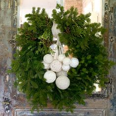 Yarn-Ball Wreath-This homespun wreath is simple and natural. Wrap foam balls in different sizes with off-white yarn. Cover each ball thoroughly, using a pushpin to secure the end of the yarn in place. Leave different lengths of yarn to hang the orbs in a layered fashion from the top of the wreath