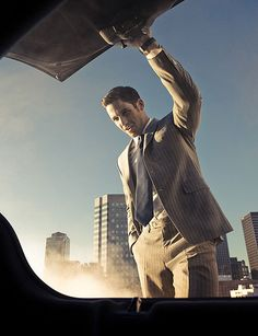 Interesting perspective - from the boot of a car! The cityscape in the background adds to the shot, as does the smoke from the exhaust. Portrait Photography Men, Photography Poses For Men, Portrait Poses, Glamour Photography, Modeling Photography, Fashion Photography, Men Fashion Photoshoot, Fashion Portraits, Photo Poses For Boy