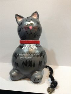 This grey stripped kitty is hand painted and has a yarn tail with a little heart at the end that says Hand made with love, and has a red