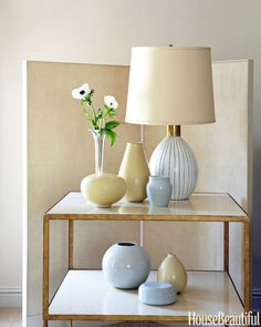 An Alastair side table in gold leaf and crackled ivory from Dessin Fournir holds a collection of ceramics that reflect the palette of the house in simple sculpted shapes.   - HouseBeautiful.com