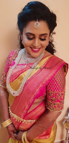 Swati is all smiles after her makeover for her reception. Hair and makeup by Team Swank. South Indian bride. Indian bridal makeup. Bridal silk saree. Saree blouse design. Bridal jewellery. Pink lips.