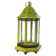 """Illuminate your front doorstep with this eye-catching design, perfect for welcoming guests or enjoying summer evenings on the porch.   Product: LanternConstruction Material: Metal and glassColor: GreenAccommodates: (1) Pillar candle - not includedDimensions: 20.19"""" H x 11.18"""" W x 11.18"""" D"""