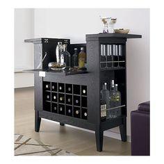 Parker Spirits Cabinet. Two bartop leaves flip open to perch drinks and snacks, while revealing generous bottle storage. Front door drops down to create an open serving area. Below are a drawer for tools and an 18-bottle wine bin. Side shelves (three on the left, two on the right) store stemware or bottles. Finished back panel lets Parker be the center of the party.