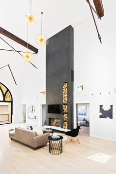Industrial, black and white living space with cool firewood storage, fireplace, industrial lighting, and high ceilings